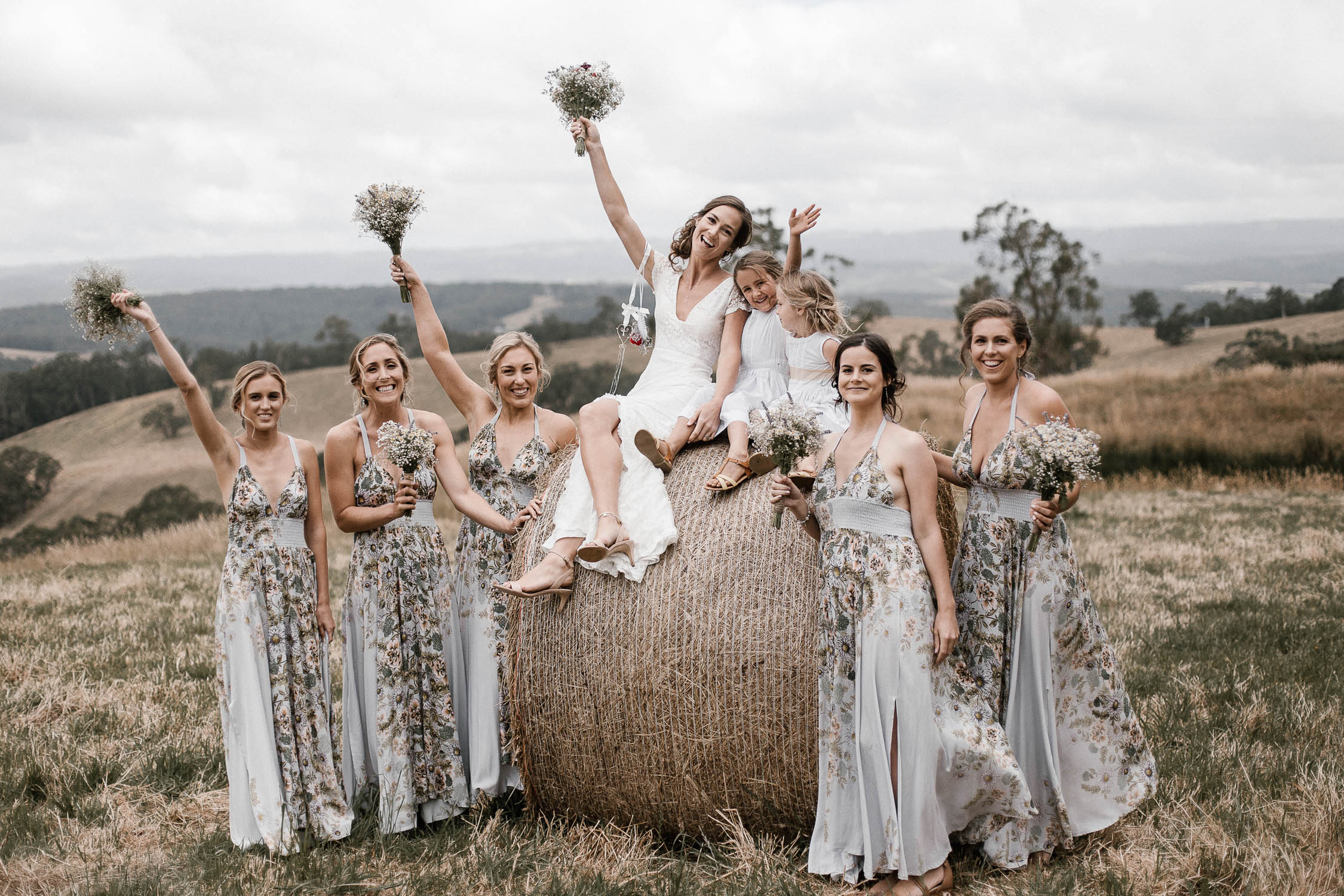 Bridal party with floral pattern dresses and the bride Marlana in Kawarren posing on top of a haystack