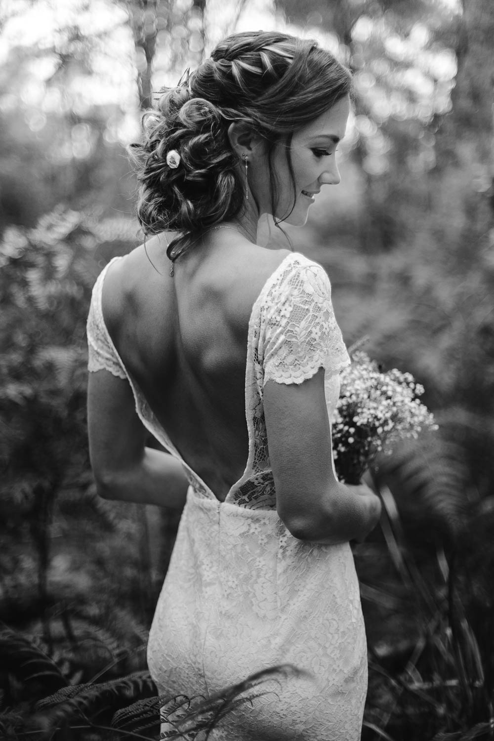 Stunning bohemian bride posing with her back towards the camera in the forest